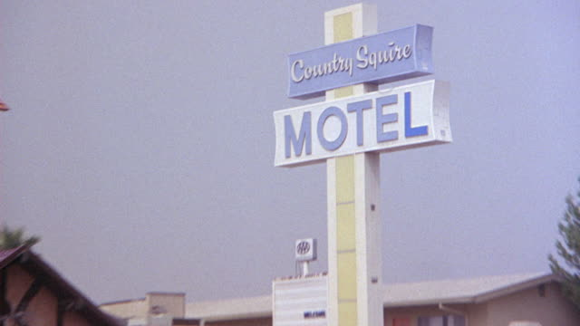 medium angle of motel on side of city street. see cars passing by in either direction and pedestrian walking on sidewalk. - motel stock videos and b-roll footage