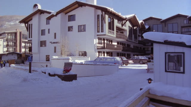 MEDIUM ANGLE OF SKI RESORT LODGING. SEE PEOPLE BEING CARRIED ON HORSE DRAWN CARRIAGE AND PERSON WALKING CARRYING SNOW GEAR TOWARDS LODGE.