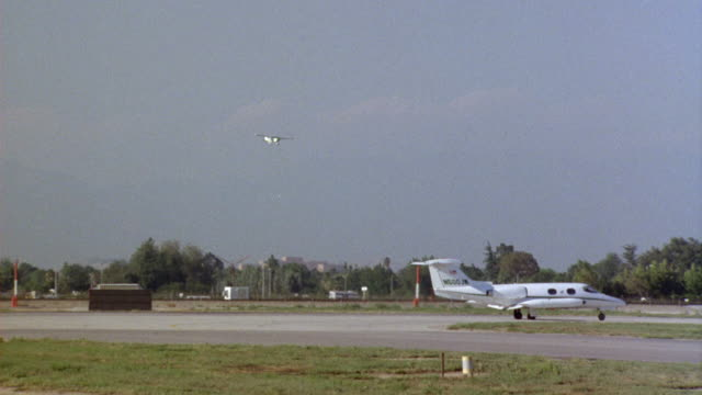tracking shot of  single enging airplane landing on tarmac, airport runway. white private jet parked on tarmac in foreground. - runway stock videos and b-roll footage