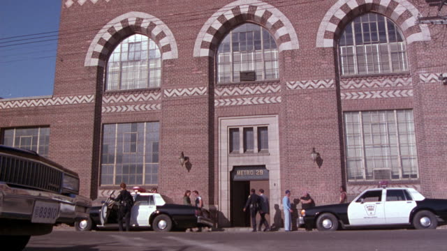 "medium angle of two story brick building. see chevron designs between levels. police cars parked out front. see ""metro 29"" sign above entrance doors. probably police station. - philadelphia pennsylvania video stock e b–roll"