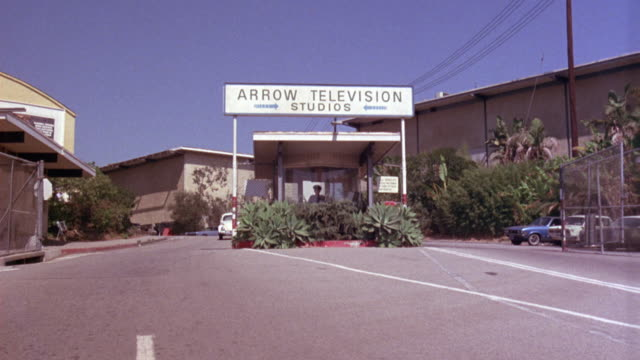 "MEDIUM ANGLE ESTABLISH KIOSK WITH ""ARROW TELEVISION STUDIOS"" SIGN ON TOP GUARD INSIDE. SEE STUDIO BUILDINGS IN BACKGROUND."