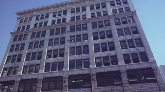 UP ANGLE OF MULTI-STORY OFFICE BUILDING. SEE CLASSICAL CORNICE OVERHANG AT TOP. SEE DIAMOND DESIGN BETWEEN PILASTERS.