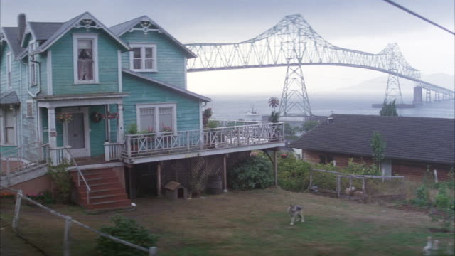 wide angle of coastal victorian two story sea green home on stilts. see ducks and dog in front yard. metal suspension bridge in right background. overcast. - 19th century style stock videos & royalty-free footage