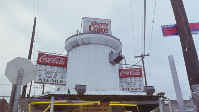"medium angle restaurant, see ""coca-cola"" signs hanging over either side of round stove vent with ""pat's king of steaks"" beneath. pan down, see people sitting at outdoor tables. people wave towards camera. - two dimensional shape stock videos and b-roll footage"