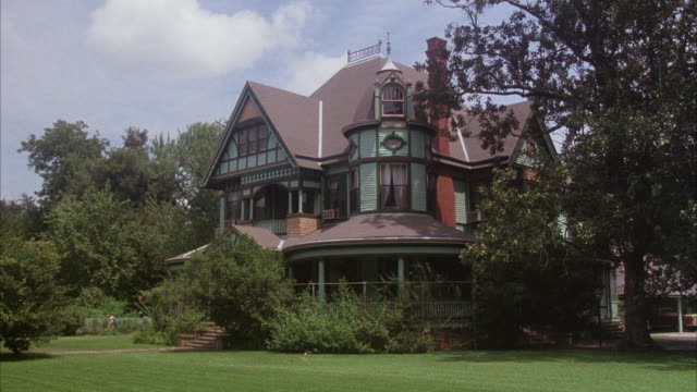 MEDIUM ANGLE, MULTI STORY TURQUOISE VICTORIAN MANSION WITH BROWN ROOF AND TUDOR STYLE ELEMENTS.