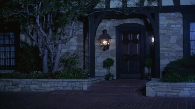 vídeos de stock, filmes e b-roll de medium angle entrance facade of fieldstone tudor style house. see lit lantern hanging beside entrance door. - facade