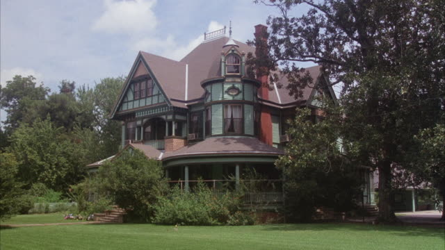 MEDIUM ANGLE, MULTI STORY TURQUOISE VICTORIAN MANSION WITH BROWN ROOF AND TUDOR STYLE ELEMENTS. SEE SEVERAL ROUNDED PORCHES AROUND HOME.