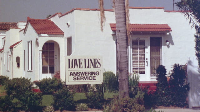 ZOOM IN FROM OLDER WHITE ONE STORY SPANISH STYLE OFFICE BUILDING WITH RED TILE ROOF TO 'LOVE LINES ANSWERING SERVICE' SIGN.