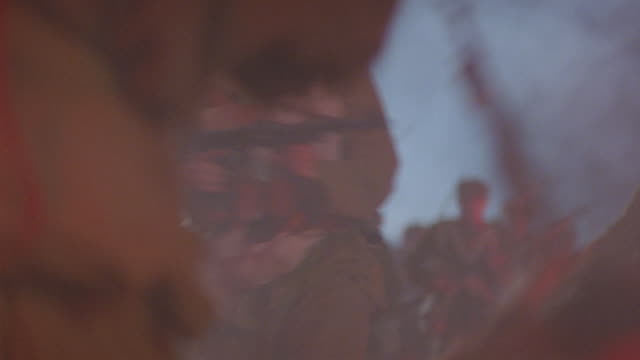 HAND HELD OF BATTLEFIELD ATTACK. SEE BACKS OF (TIBETAN) SOLDIERS BEHIND BARRICADE AS THEY AIM RIFLES AT ATTACKING SOLDIERS.