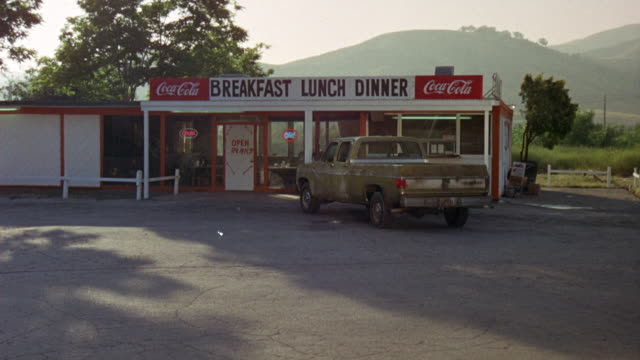 "medium angle of truck stop and parking lot. green ford pickup truck in lot. signs on diner or restaurant read ""breakfast lunch dinner"" and ""open 24 hrs"" with coca-cola logos. - ford truck stock videos and b-roll footage"