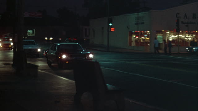 pan right of cars driving down street. see police car turn onto street, then make u-turn, put flashing lights on and make right turn at corner. - police car stock videos and b-roll footage