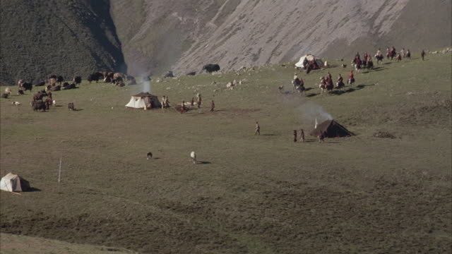MEDIUM ANGLE OF VILLAGE OR CAMP IN VALLEY. SEE FEW HORSES OR DOMESTIC ANIMALS AMIDST SOME BROWN AND WHITE TENTS.
