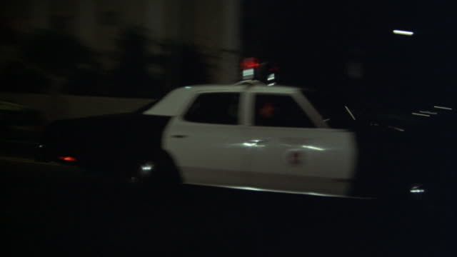 pan right of police car driving down street. - moving activity stock videos & royalty-free footage