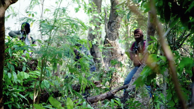 medium angle of several insurgents or rebels or gunmen firing machine guns from behind trees in a jungle or forest. - ski clothing stock videos and b-roll footage