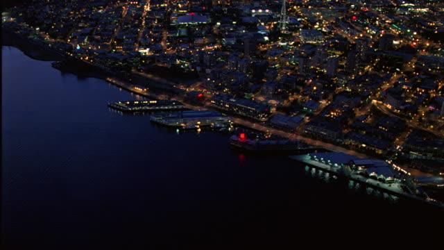 vídeos de stock e filmes b-roll de aerial of docks on puget sound in front of seattle center and space needle in downtown seattle. camera descends to multi-story waterfront office building. seattle skylines. - pacífico norte