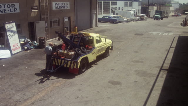 """high angle down, see man standing next to yellow tow truck. see building at left with signs  """"auto repair"""" and """"wheels aligned."""" - tow truck stock videos and b-roll footage"""
