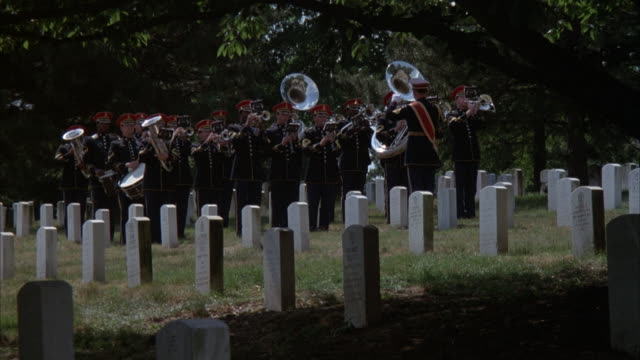 MEDIUM ANGLE OF MILITARY BAND IN ARLINGTON CEMETERY. CONDUCTOR TURNS AROUND AS BAND MEMBERS LIFT INSTRUMENTS AND PLAY INSTRUMENTS. CONDUCTOR TURNS AROUND AS INSTRUMENTS ARE PUT DOWN. HEADSTONES AND TREE IN FOREGROUND.