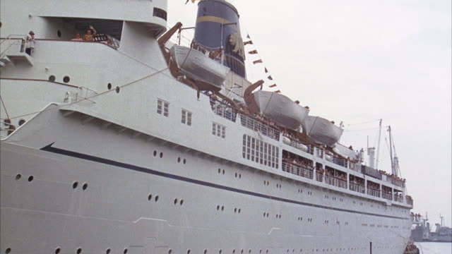 """up angle of white cruise ship. see two people on upper level waving. pan right, see body of ship, life boats hanging from side, people standing at rails. zoom out see ship continue to move away from pov. see """"monterey"""" painted on body of ship. - kreuzfahrtschiff stock-videos und b-roll-filmmaterial"""