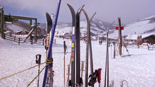 MEDIUM ANGLE SKI HILLS. SEE SKIS IN FOREGROUND, SKI LIFT, MOUNTAINS AND BUILDINGS IN BACKGROUND. SEE SNOWMOBILE MOVE TOWARDS POV.