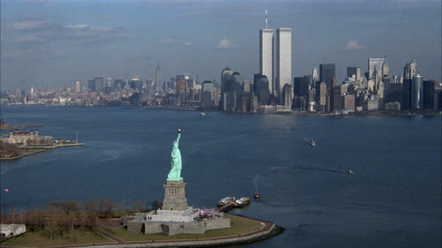 wide angle aerial of statue of liberty in foreground with new york city skyline in background with world trade center. zooms in on skyline at end. - world trade center manhattan stock videos and b-roll footage
