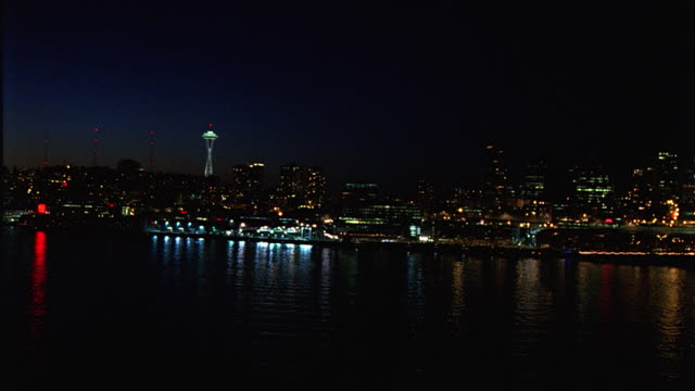 vídeos de stock, filmes e b-roll de wide angle of downtown seattle skyline with space needle and radio antenna towers in background. see light from waterfront buildings and docks reflect off puget sound. - pacífico norte