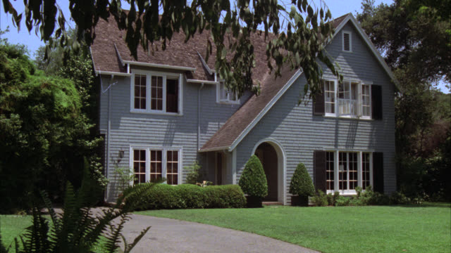 wide angle of two story middle class suburban house. shingle style. arched doorway. trees. driveway visible. - zweistöckiges wohnhaus stock-videos und b-roll-filmmaterial
