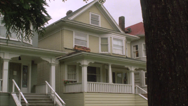 medium angle of three story house with front porch. could be middle or upper class. suburbs or residential area. - stereotypically middle class stock videos & royalty-free footage