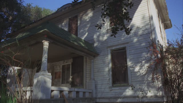 up angle of lower class two story house with front porch. abandoned or rundown. could be rural area. weeds surround porch. - architectural feature stock videos & royalty-free footage