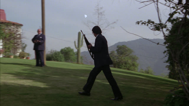 stockvideo's en b-roll-footage met wide angle of yard of upper class spanish style villa. cactus in fg. guard in suit carries gun or weapon across lawn. could be security guards. - bewakingspersoneel