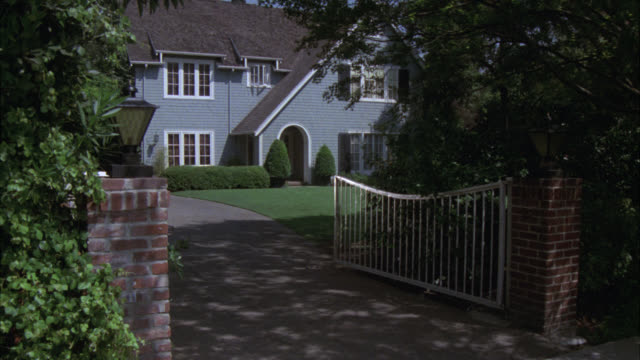 pan right to left of two story middle class shingle style house in residential area. driveway gate and light visible. - mailbox stock videos and b-roll footage