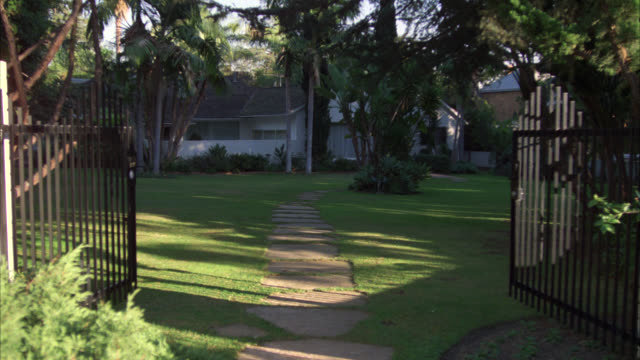 WIDE ANGLE OF RANCH HOUSE THROUGH IRON GATES. FRONT YARD OR LAWN. TREES SURROUND HOUSE.