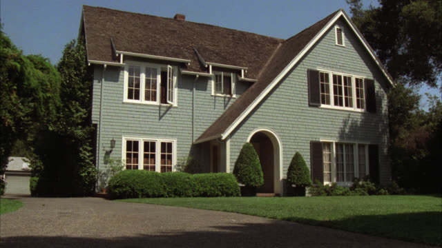 wide angle of two story middle class shingle style house. adolescent walks across front lawn with bookbag. - middle class stock videos & royalty-free footage