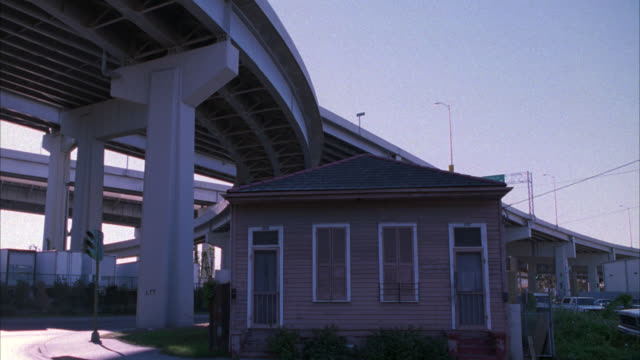 MEDIUM ANGLE OF SMALL LOWER CLASS ONE STORY HOUSE LOCATED UNDERNEATH BRIDGE OR OVERPASSES. FREEWAY OR HIGHWAY. TRUCKS VISIBLE IN STORAGE YARD IN BG.
