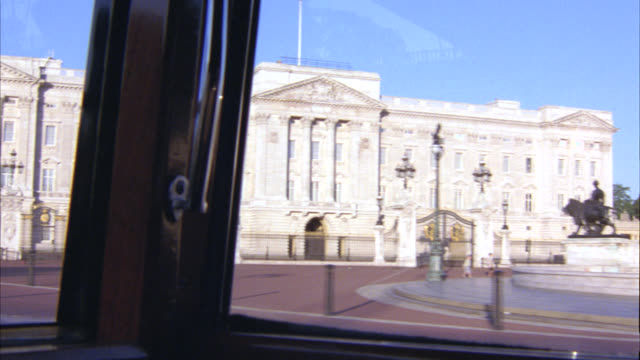 vídeos de stock, filmes e b-roll de wide angle driving pov 3/4 right forward of buckingham palace and queen victoria war memorial or monument. landmarks. upper class stone building. royalty. government building. london, england. - palácio de buckingham