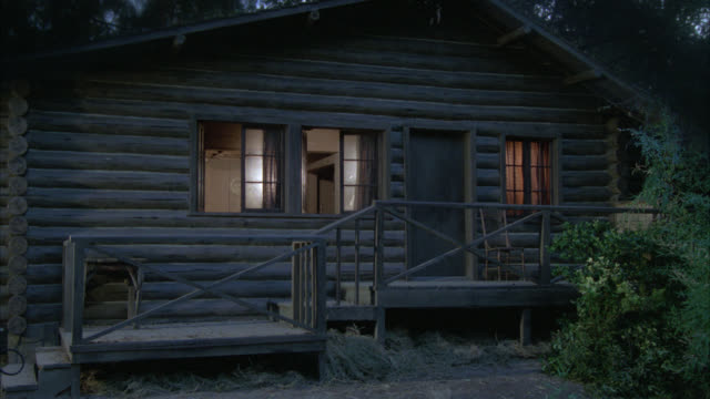 zoom in on window of one story log cabin. could be in forest, woods or mountains. - capanna di legno video stock e b–roll
