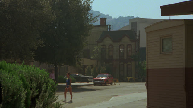 wide angle of people walking around back lot with facades. could be warner bros back lot. studios. - warner bros stock videos and b-roll footage