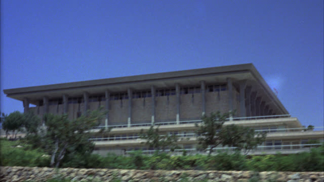 wide angle driving pov 3/4 right forward of stone building on hill. john f. kennedy palace. could be theater or concert hall. middle east. - concert hall stock videos and b-roll footage