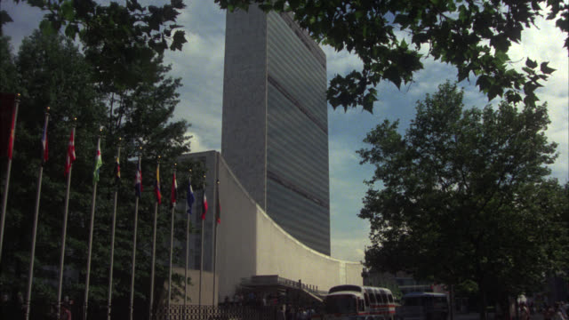 zoom in on high rise united nations headquarters building, office building. flags on flagpoles in fg. - united nations building stock videos and b-roll footage