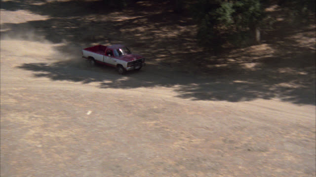 aerial of red and white pickup truck driving along dirt country road up to ranch house, cabin, or lodge. trees. - ranch home stock videos & royalty-free footage