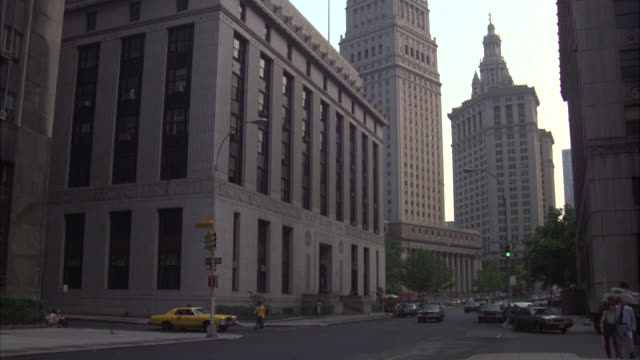 pan right to left of cars driving on nyc street past multi-story buildings, government buildings. car pulls up to criminal courts building, man exits building and walks toward building. - courthouse stock videos & royalty-free footage