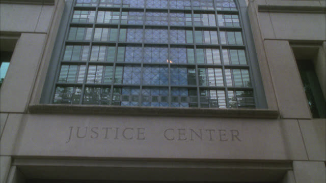 """pan down from window and """"justice building"""" etched in stone to people walking in and out of entrance to building. - portland oregon bildbanksvideor och videomaterial från bakom kulisserna"""