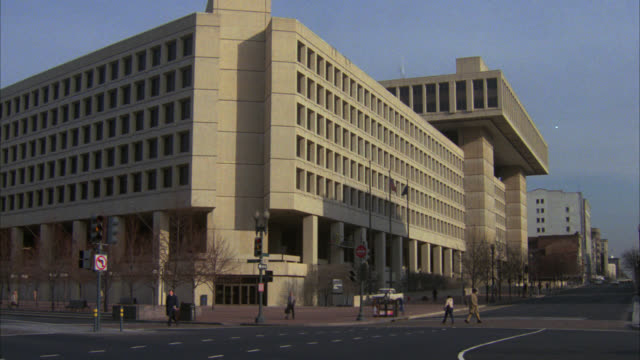 zoom in on window of multi-story fbi building, government building. cars driving by and people walking on sidewalk in fg. - fbi stock videos & royalty-free footage