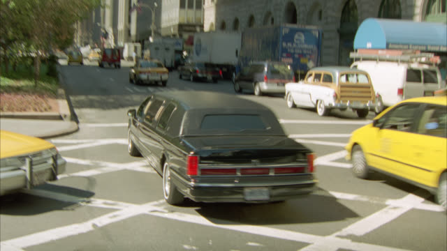pan up from cars, taxis and a limo driving on nyc street to high rise and skyscraper office buildings, metlife building and helmsley building in bg. city streets. cities. park avenue. - 2001 stock videos and b-roll footage