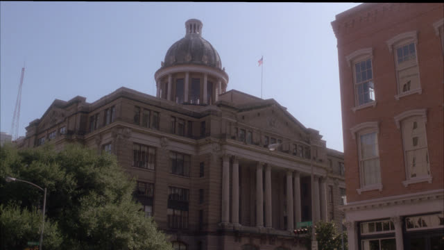 stockvideo's en b-roll-footage met wide angle of multi-story harris county courthouse building with domed roof or cupola and columns. government buildings. cars driving through intersection past building in fg. cities. could be small town. - 1991