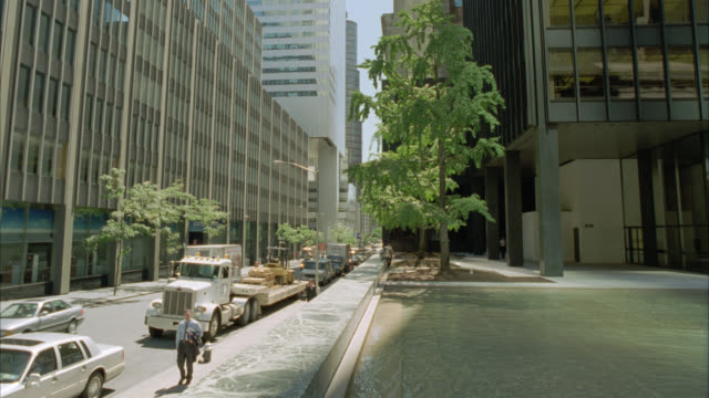 wide angle of cars driving on one way city street. pedestrians, people walking on sidewalk and high rise and skyscraper office buildings on both sides of street. new york city. nyc streets. - 2001 stock videos and b-roll footage