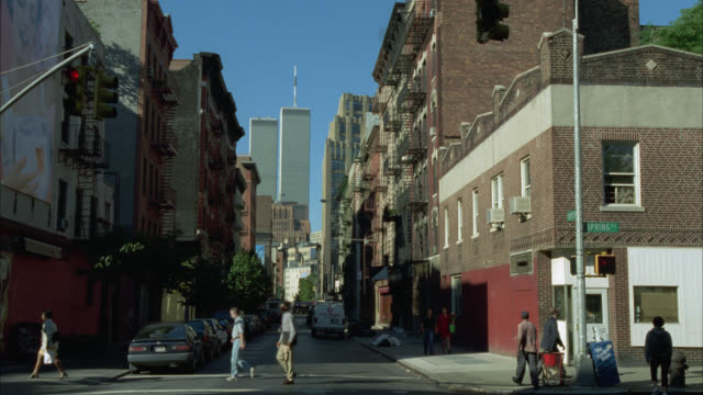 medium angle of city street. multi-story brick apartment buildings lining sides of street. cars and pedestrians pass by. world trade center or twin towers in background. skyscrapers or high rise office buildings. new york city. manhattan. - 2001 stock videos and b-roll footage