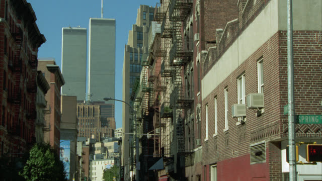 medium angle of city street. see brick buildings lining side of street. could be apartment buildings. see spring st sign. see world trade center or twin towers in background. new york city or manhattan. - world trade center manhattan video stock e b–roll