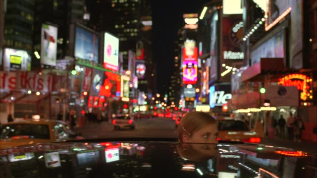 up angle moving pov driving on city street in times square. pov from open sunroof of black limousine limo. two young women pop their heads up and back down. billboards, advertisements and neon lights. phantom of the opera poster. commercial area. manhatta - limousine stock videos & royalty-free footage