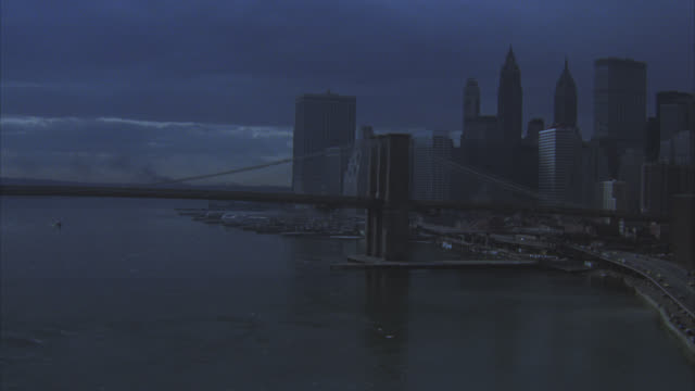 zoom in from brooklyn bridge over east river and new york city skyline to cadillac car driving on franklin delano roosevelt drive. skyscrapers and high rise office buildings. downtown. manhattan. - 1981 stock-videos und b-roll-filmmaterial