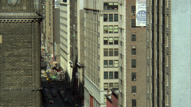 """vídeos de stock e filmes b-roll de pan down from skyscrapers and high rises to brick apartment building with open window. chrysler building visible. new york city skyline. open window with """"mike hammer private investigator"""" sign. man stands in window. traffic visible on street below. - prédio chrysler"""